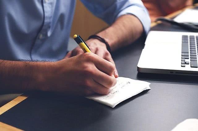 Imagem de homem escrevendo em papel