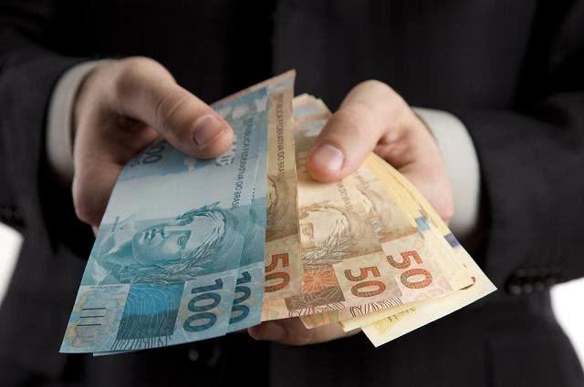 Imagem de homem de terno segurando notas de dinheiro
